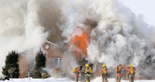 Firefighters working in front of a home billowing smoke
