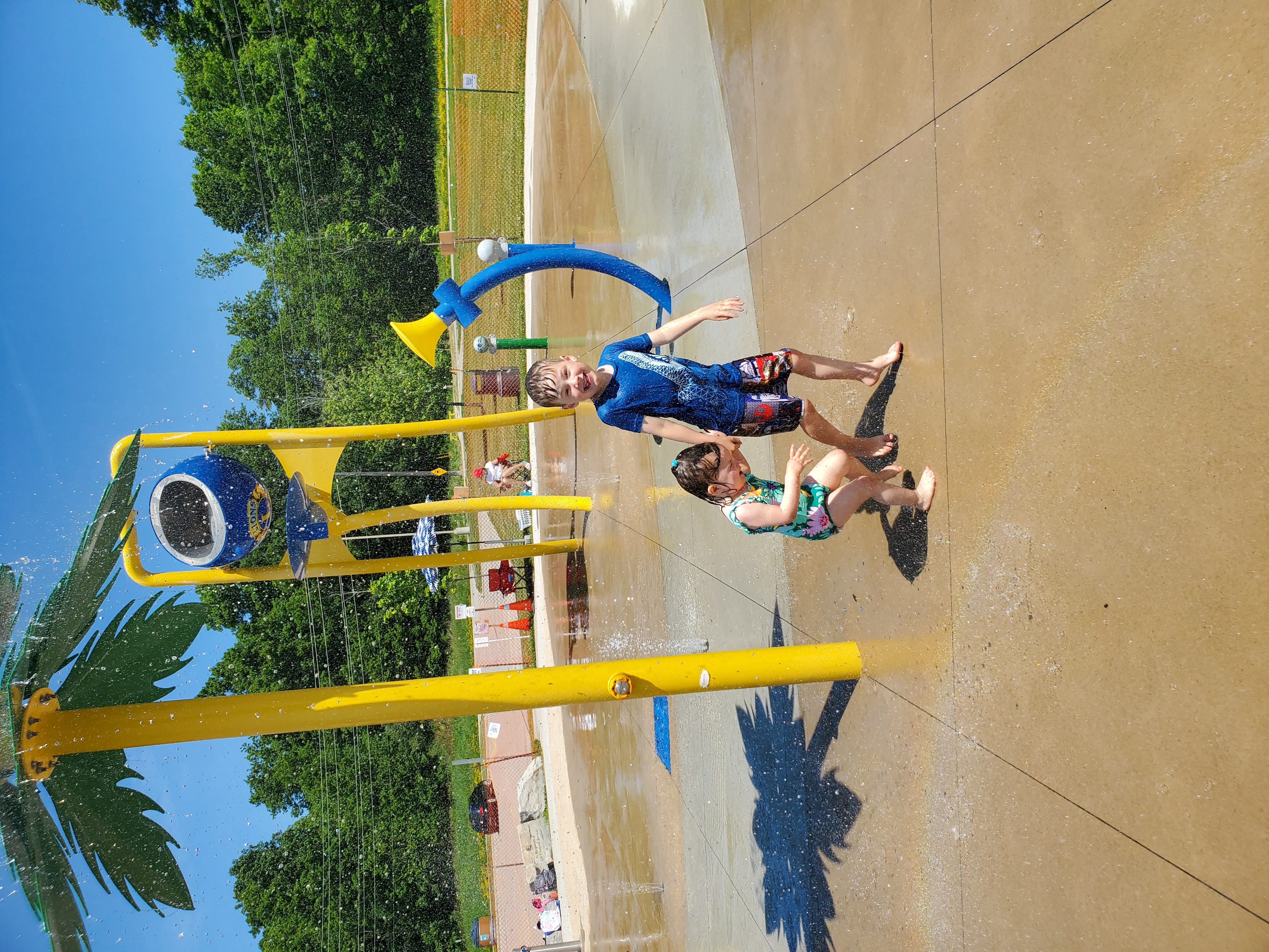 Two young children play in the splash pad under the tree water feature.