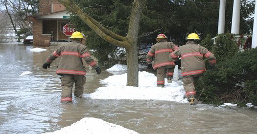 Firefighters walking through a flooded street