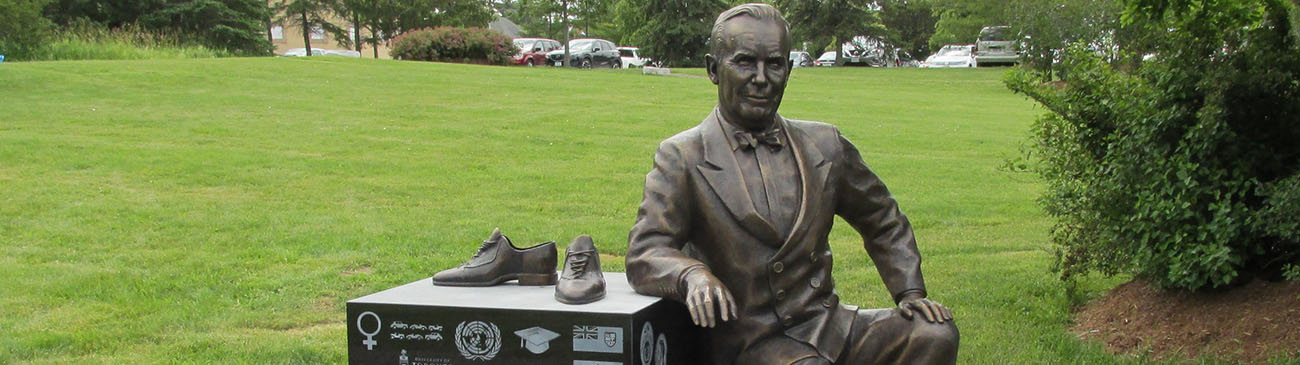 Statue of former Prime Minister Lester B. Peason relaxing against a stone base with his shoes off