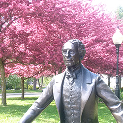 Statue of former Prime Minister Sir John A. Macdonald with trees with pink flowers