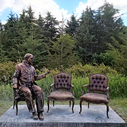 Statue of former Prime Minister William Lyon Mackenzie gesturing towards two chairs as though in conversation